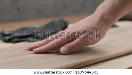 man hand touches black walnut board #1639644505