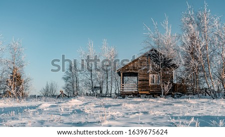 Winter season, landscape picture of a village covered by snow at sunset, country landscape with timber fence, holiday house made with wood, abandoned house, frozen trees