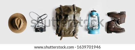 Vintage adventurer essential gear flat lay. Hat, backpack, film camera, gas lamp and boots on white background isolated. Minimal style hiking concept. Wanderlust vibes. #1639701946