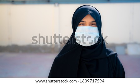 Arab muslim woman wearing face mask to protect her self from corona virus. #1639717594