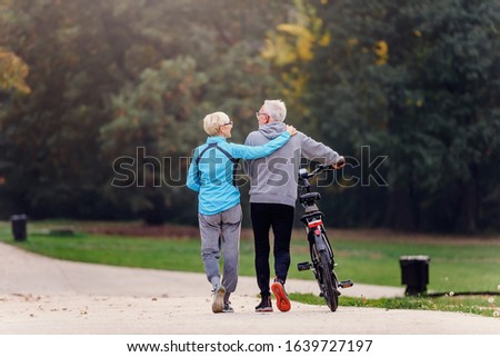 Cheerful active senior couple with bicycle walking through park together. Perfect activities for elderly people. #1639727197