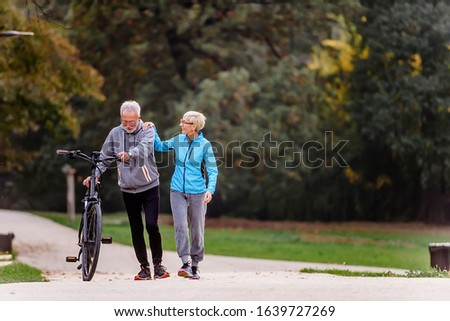 Cheerful active senior couple with bicycle walking through park together. Perfect activities for elderly people. #1639727269