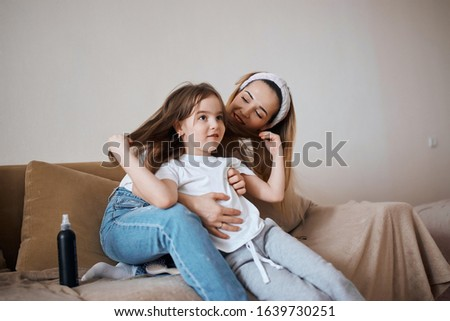 cheerful young blonde woman nd her adorable child sitting on the bed, talking, having fun, sharing secrets. close up photo, friendship, relationship