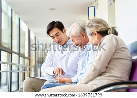 young asian doctor discussing test result and diagnosis with senior couple patients using digital tablet in hospital hallway Royalty-Free Stock Photo #1639731799