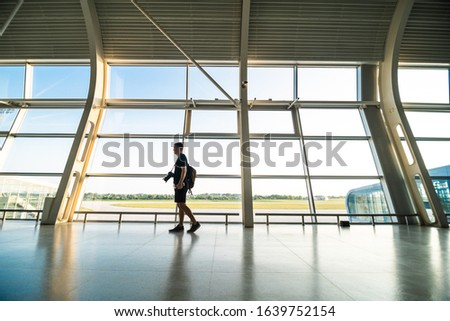 Blogger photographer making a photo of jet at runway before taking off. Concept of modern travelling and blogging.