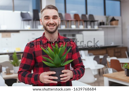 CHeerful handsome bearded man smiling to the camera, holding potted aloe, copy space. Male customer shopping at furnishing store #1639768684