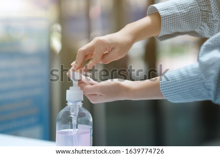 A girl using alcohol gel for cleaning hands #1639774726
