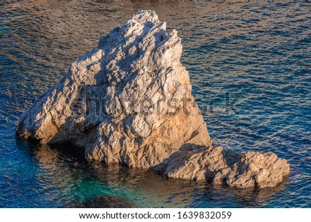 Closeup rocky rough gray cliffs of Adriatic seashore, light blue sea #1639832059