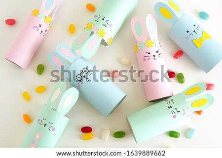 Flat lay with diy paper Easter bunnies and colorful candies, easy crafts for kids.           Royalty-Free Stock Photo #1639889662