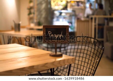 Reserved sign on a wooden table. The concept of restaurant and cafe service. Reserve space. Reserve mark. Preliminary reservation of a table in places of food. Reservation of a place for a date. #1639918486
