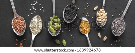 Various Seeds Assortment on black background. Set of  sesame seeds, flax seed, sunflower seeds, pumpkin seed, chia, hemp seeds in spoons, healthy food ingredients, top view, banner. #1639924678