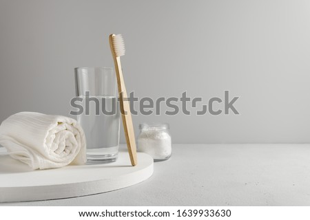 Bamboo toothbrush, glass of water, white a cotton towel and powder for brushing your teeth in jar. light gray concrete surface, gray backdrop. Biodegradable personal care products. No plastic concept. #1639933630