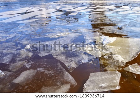 Melting ice floes on the river, lit by the sun #1639936714