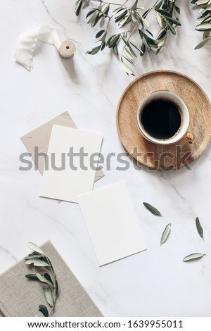 Summer wedding stationery mock-up scene. Blank greeting cards, wooden plate, book, ribbon, cup of coffee and olive branches. White table background with shadows. Vertical feminine flat lay, top view.