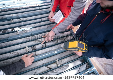 geological gold core samples with team of mining  workers measuring drilled rock top view Royalty-Free Stock Photo #1639957606