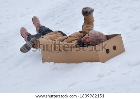 Girl riding snow hill. Slip in box in mountains. Fun winter games. Sports winter. Funny photo of child. Girl in box on snow. Winter sports holidays. Happy child in Christmas. Happy kid in box autdoor.