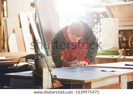 Process of production and manufacture of wooden furniture in furniture factory. Worker carpenter man in overalls processes wood on special equipment #1639975471