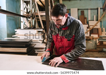 Process of production and manufacture of wooden furniture in furniture factory. Worker carpenter man in overalls processes wood on special equipment #1639975474