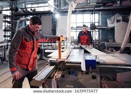 Process of production and manufacture of wooden furniture in furniture factory. Worker carpenter man in overalls processes wood on special equipment #1639975477