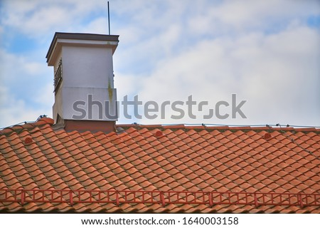 Overlapping rows of red tiles roof with chimneys in Poland, ridge tiling material regular pattern background in horizontal orientation, nobody. Royalty-Free Stock Photo #1640003158