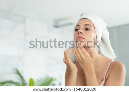 Young beautiful woman wearing bath towel and underwear standing in bathroom and looking for or squeezing acne on chin. Mirror reflection. Ugly problem teen girl skin, pimples. Skincare and beauty #1640012020