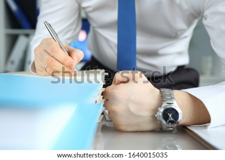 Verification documentation auditor, morning audit. Close-up man in shirt with tie checks large stack paper. Documents are on table, men are making notes. Concept internal audit company. #1640015035