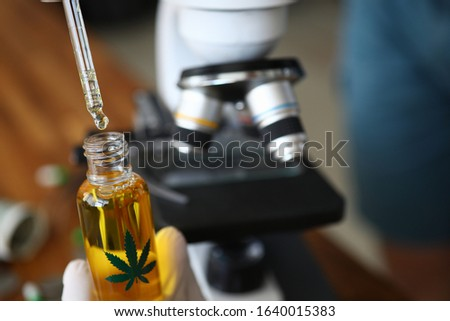 Taking expertise for manufacture pharmaceuticals. On cone with liquid leaf hemp is represented. Pipette picks up small drop from bottle. In background microskim for conducting experiment. #1640015383