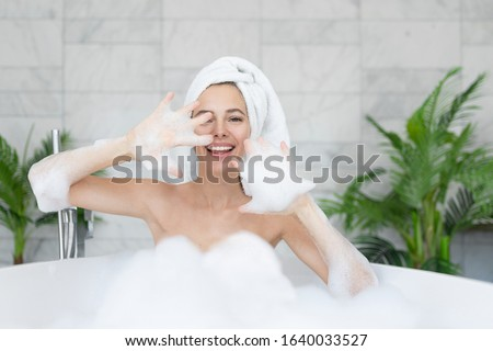 Smiling woman play with foam in bathtub. Portrait of beautiful girl in playful mood. Female character taking bath and having fun. Home bathroom. Beauty and personal hygiene, rest and relax #1640033527