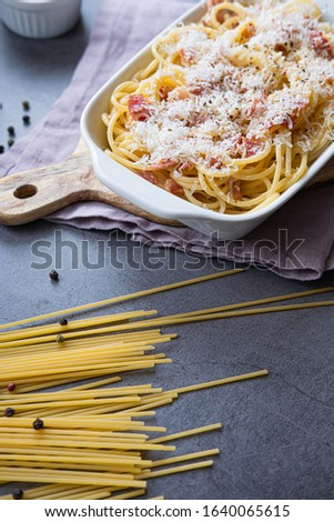 Italian pasta carbonara with bacon, parmesan cheese and egg on a white ceramic dish. Italian cuisne. Vertical picture.