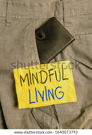 Word writing text Mindful Living. Business concept for Having a sense of purpose and setting goals in life Small little wallet inside man trousers front pocket near notation paper. #1640073793