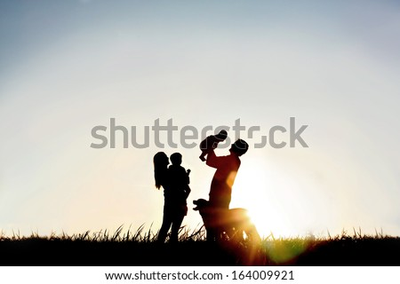 A silhouette of a happy family of four people, mother, father, baby, and child, and their dog in front of a sunsetting sky, with room four copy space or text