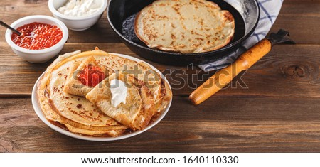 Traditional Russian Crepes Blini stacked in a plate with red caviar, fresh sour creamon dark wooden table. Maslenitsa traditional Russian festival meal. Russian food, russian kitchen. Long wide banner Royalty-Free Stock Photo #1640110330