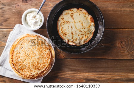 Traditional Russian Crepes Blini stacked in a plate and pancake in a cast-iron frying pan on dark wooden table. Maslenitsa traditional Russian festival meal. Russian food, russian kitchen. Top view. #1640110339