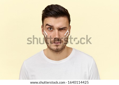 Human emotions, reaction and feelings. Unhappy furious young man with angry facial expression, frowning eyebrows, expressing annoyance posing isolated with white stripes of shaving foam on cheeks #1640114425