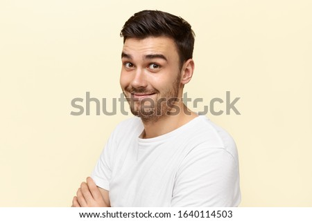 Emotional surprised young Caucasian man with bristle raising eyebrows having astonished facial expression impressed with intriguing news, expressing true emotions, posing isolated in white t-shirt #1640114503