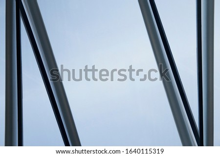 Glass wall with metal framework. Minimalist windows. Office building exterior or interior fragment. Abstract modern architecture background with geometric structure and blue sky. Structural glazing. #1640115319