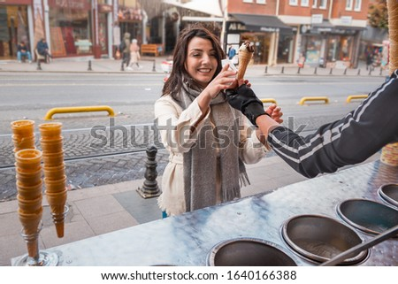 Beautiful young girl in fashionable clothes laughs because of Ice cream seller man playing traditional Turkish joke in Istanbul,Turkey #1640166388