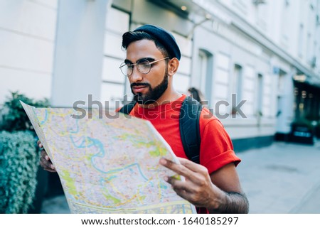 Focused serious male in glasses and with backpack focusing on paper map while walking on street of modern city traveling alone #1640185297