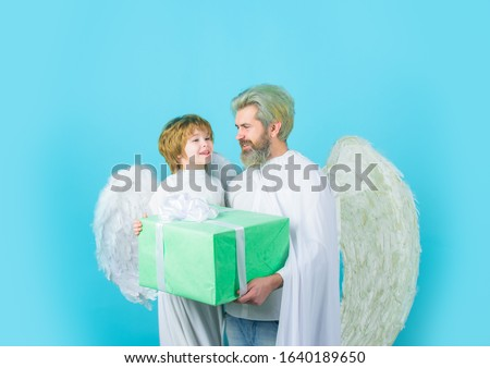 Father's day. Little angel son gives father gift. Happy father in angel costume with little son angel holds present. Cute angel. Father and son Angels. Valentines day. Valentines angels with gift box. #1640189650
