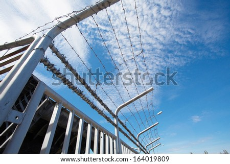 Barbed wire fence against the blue sky #164019809