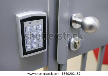 Closeup of electronic lock with keypad  and steel bobble handle on metal bar security door Royalty-Free Stock Photo #1640203189