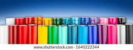 Row of various rainbow colored vinyl car wrapping or plotter cutting sticker foil film rolls on blue white wide panorama banner background Royalty-Free Stock Photo #1640222344