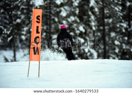 Orange slow caution sign with skier on downhill run #1640279533