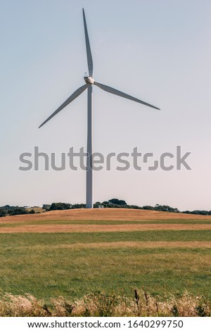 A wind turbine or windmill on a beautiful meadow. Blue sky and yellow and green fields creates a well color balanced picture. Renewable energies are replacing fossil fuels all over the world.