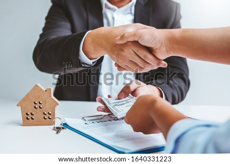 Sale Agent handshake with woman customer and sign agreement documents for realty purchase after successful loan contract #1640331223
