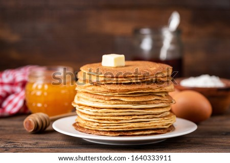 Blini or crepe or thin pancakes stack on wooden table topped with butter. Shrove Tuesday, Maslenitsa holiday concept. Rustic style breakfast Royalty-Free Stock Photo #1640333911