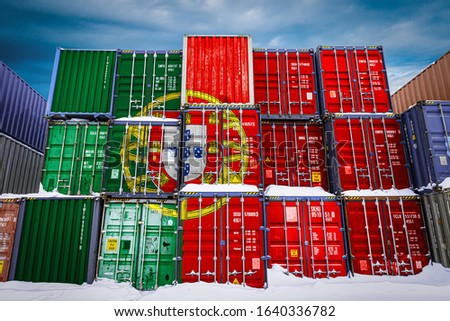 The national flag of Portugal on a large number of metal containers for storing goods stacked in rows on top of each other. Conception of storage of goods by importers, exporters