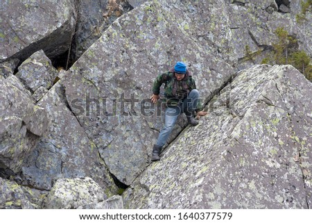 Southern Urals. A mature tourist makes an ascent to the top along a large stone placer. #1640377579