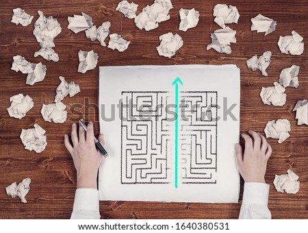 Shortcut of a maze drawn on paper . Crumpled papers arround. Easy solution of a difficult problem. Royalty-Free Stock Photo #1640380531