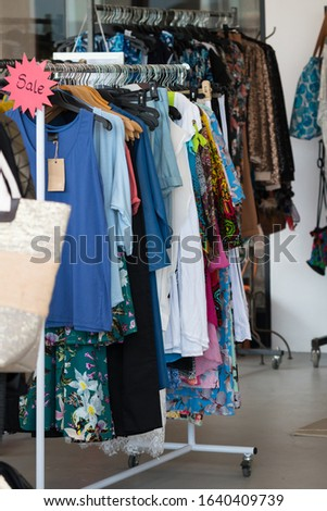 end of season summer sale, clothes hang on a rack in a dress shop or boutique for stock clearance